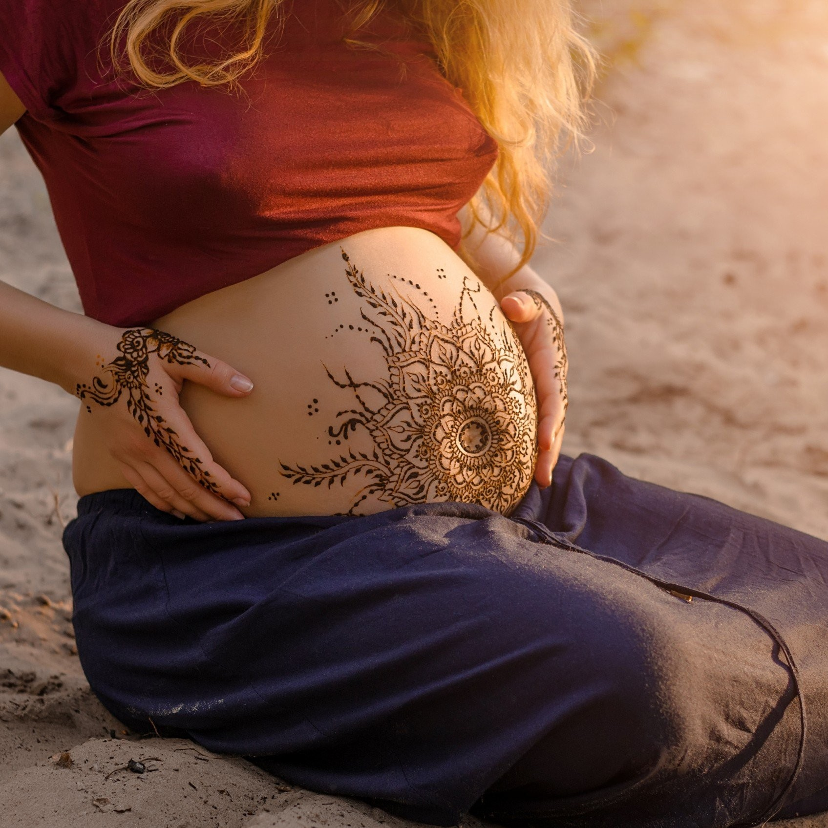 Pregnant woman with mehendi henna tattoo on her belly and hands, cropped image, hands on pregnant tummy. Motherhood concept, happy maternity